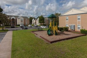 Children's play park with slide, woodchips, and bench next to parking lot and Ravenna's exterior