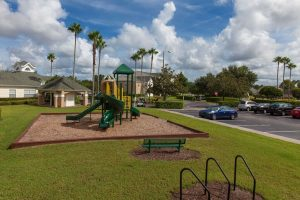 Children's play park with slide, woodchips, and bench next to parking lot